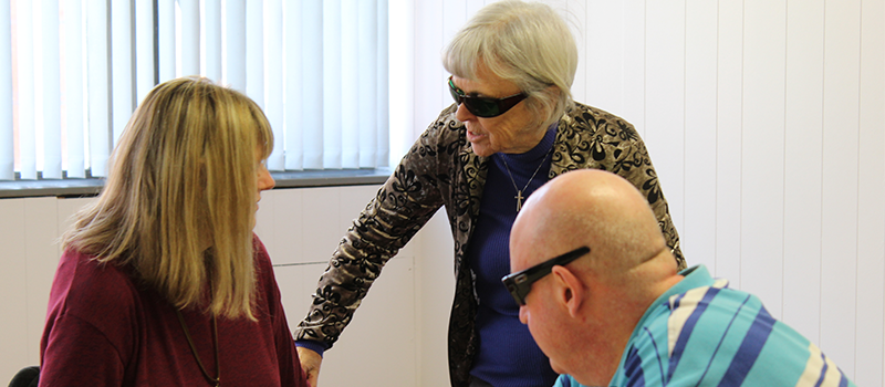 Photograph of our Chair Andrea talking to 2 members of our social group, Jackie and Paul. Jackie is stood up and Paul and Andrea are sat down