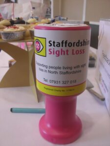 Photo of a pink Staffordshire Sight Loss collection box on a table, in the background there is a table of cakes for a cake stall to raise money