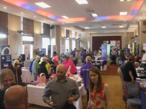 Photograph of our 2019 Awareness Event at the Quality Hotel, there are lots of information stands and people walking around and chatting to eachother