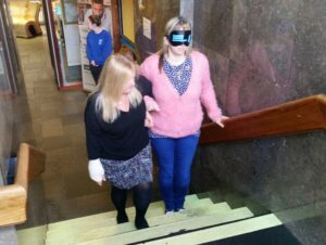 Photo shows a lady in a pink jumper wearing a blind fold being guided up some steps by another lady