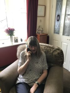 Photograph of Andrea who is our Chair but also a telephone befriender, sat on a chair talking on the phone