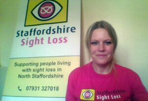 Photograph of Service Manager Suzanne, wearing a pink Staffordshire Sight Loss t-shirt sat next to a Staffordshire Sight Loss roller banner