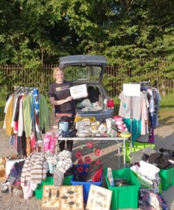 photograph of Service Manager Suzanne at a car boot selling items, and holding a sign which says 'all proceeds donated to Staffordshire Sight Loss Association'. She has a table full of items to sell and the table is also surrounded by items